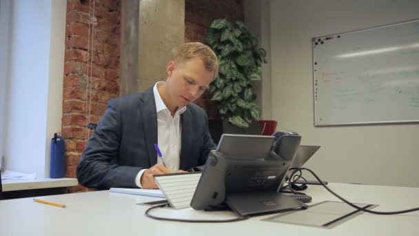 Male boss writes in notebook while sitting in own office.