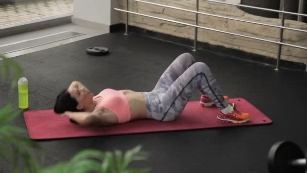 Woman on mat trains and carefully pumps press on stomach in gym.