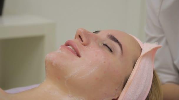 Kosmetikerin reinigt Gesicht junger Frau in Klinik.