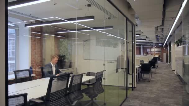 Obchodní pracovníci pracují v prostorné kanceláři se skleněné výplně.