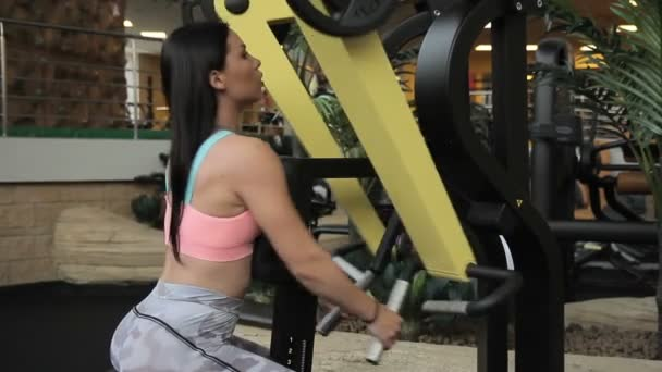 Female athlete doing row machine exercise in gym.
