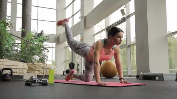 Frau im Fitnessraum winkt Fuß auf allen Vieren.