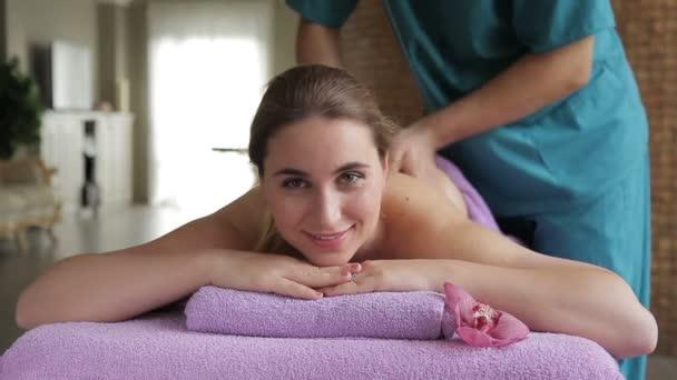 Žena úsměvy při masáži, která se provádí odborník v salonu.