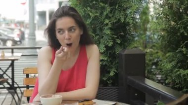 The portrait of beautiful young woman who sits in the outdoor cafe and eats cake by the fork.