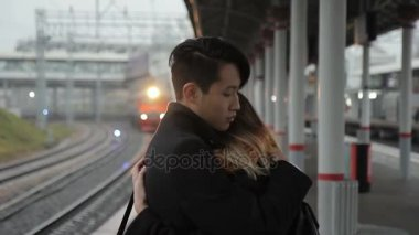 Young man is hugging woman standing at railway station outdoors. multiethnic