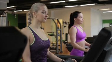 Two young sportswomen are walking on the treadmill in modern gym.