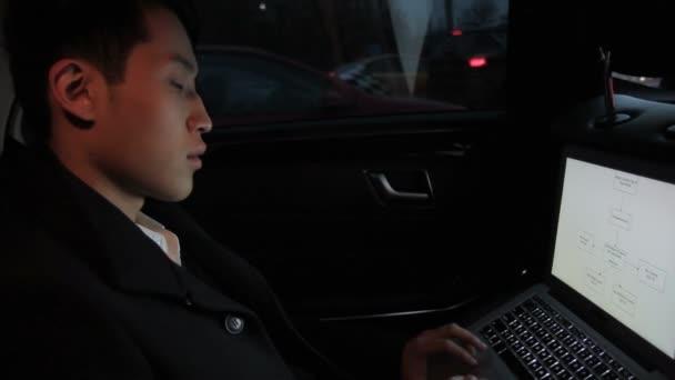 Uomo coreano con il computer portatile è seduto in macchina.