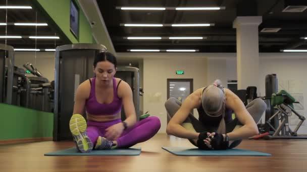 Két női barátaim csinálnak nyújtó gyakorlatok jóga modern edzőteremben előtt