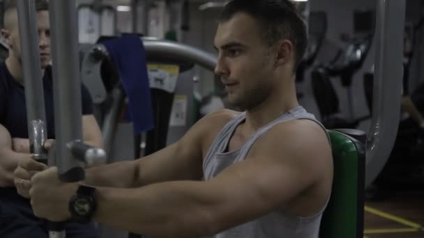 Male bodybuilder is working on his arm muscules in the gym and his couch is controlling his training.