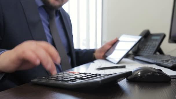 Mužské specialista provede výpočty na kalkulačce a píše, sedět ve společnosti