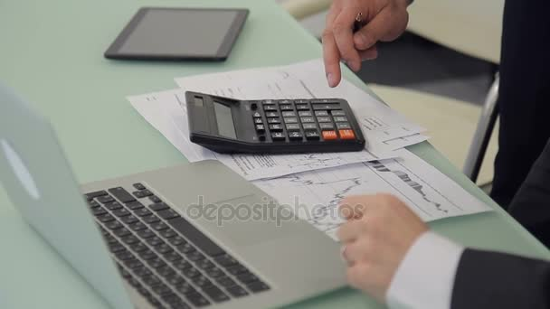 Close-up of business people are counting on calculator on desktop.