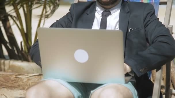 Businessman is writing a report on his laptop in tropical beach.