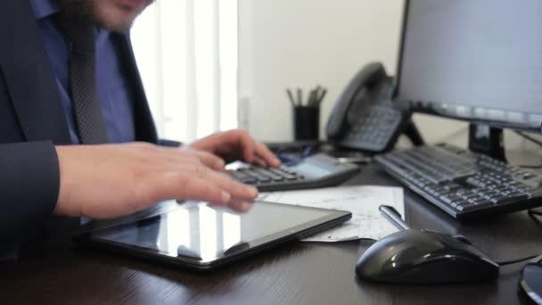 Der Chef scrollt der Bildschirm sein Tablet von seiner Hand, auf der Suche nach Daten und setzt es auf den Rechner