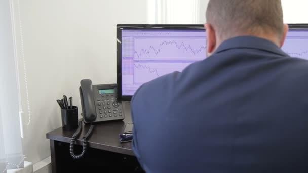 Az ember ül íróasztal és tanulmányok pénzügyi két monitor a grafikonok.