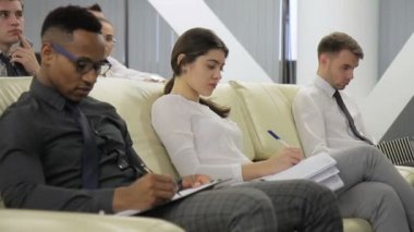 Tho businessmen and businesswoman take notes sitting on the conference in modern bright office.