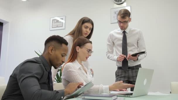 Mladí profesionálové pracují ve firmě, pomocí notebooku a tabletu
