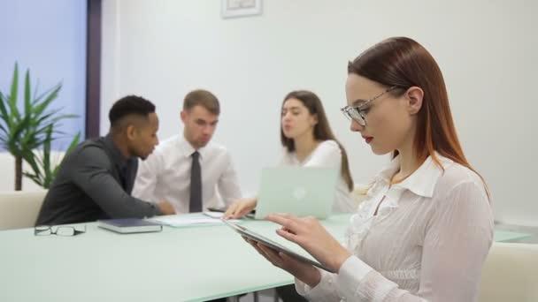 Die Geschäftsfrau scrollt der Bildschirm des Tablets und lächelt, während preraring für die Präsentation