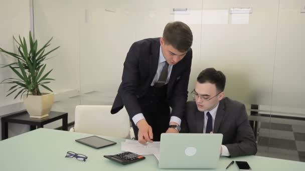 Dva podnikatelé mluví u stolu ve velké společnosti.