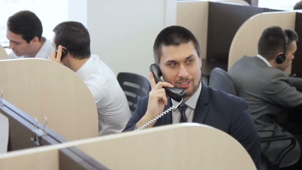 Young specialist is talking on phone while sitting in promising company.