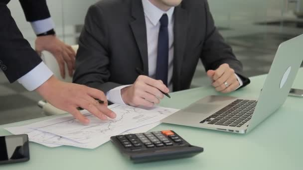 A pair of brokers compare the exchange rates charts on the paper with the results on the laptop.