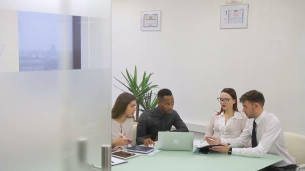 Mladí zaměstnanci pracují na stůl s notebookem v interiéru velké společnosti