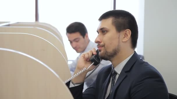 Male operator makes phone call while sitting in modern office.