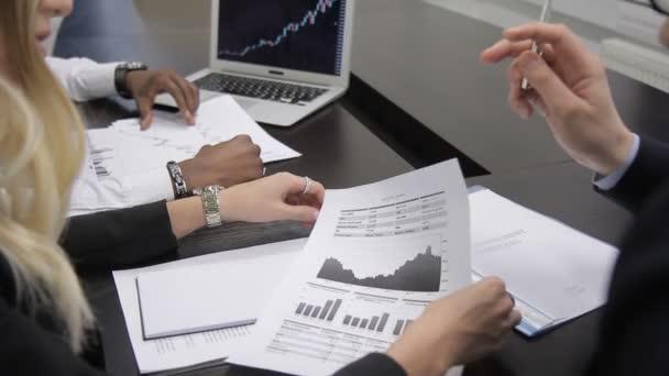 Na stole v kanceláři mezinárodní tým aktivně diskutuje o grafiku na papíře