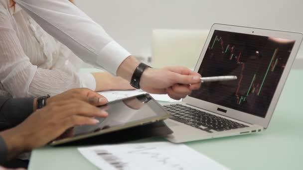 Mladí zaměstnanci používají notebook a tablet, sedící v přední společnosti