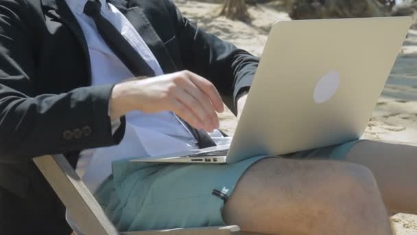 Businessman is sitting on the beach with laptop on his knees.