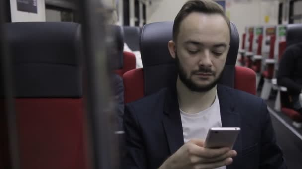 Man with beard in the bus chair reads from the smartphone screen.