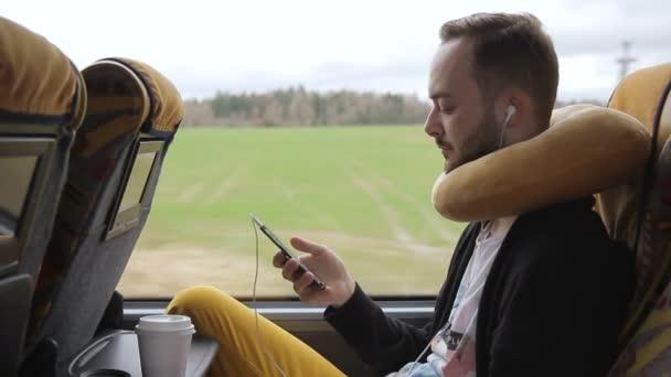 Fiatal ember tart smartphone délután busszal utazás közben.