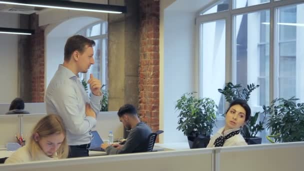 Young man and woman talking in modern office.