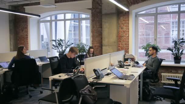 V úřadu zaměstnanci vzájemně komunikují sedíte za stolem.