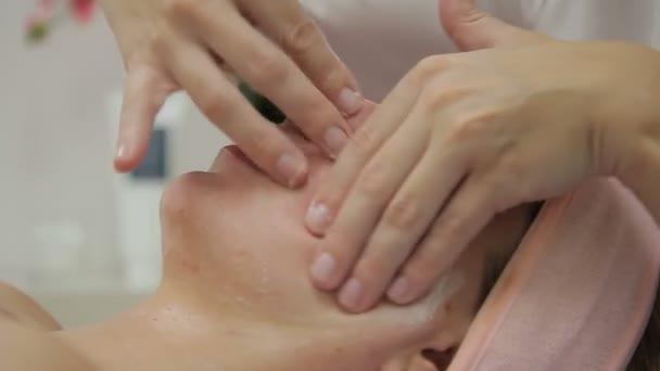 Kosmetička se masáž obličeje s ženou v salonu krásy