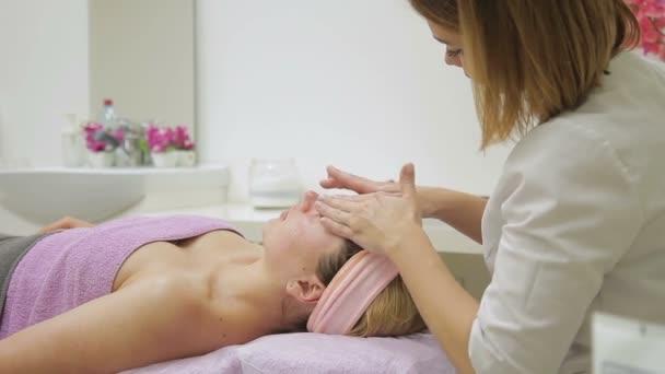 Žena terapeut masáže tvář lhaní lady v lázeňském centru