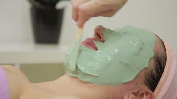 Kozmetikus hozza mask arcán nő a szépségszalon.