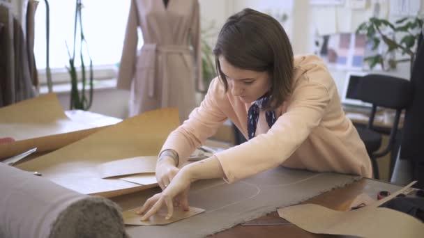 Femmina giovane sarto è fare marcature sul tessuto con il gesso, in piedi al tavolo in studio di cucito, stilista è in processo di lavorazione con tessuto alla scrivania, fittizio in vestito in camera luminosa.