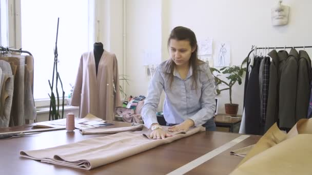 Female clothing designer is laying clothes, standing at table, colleague is making notes, women are working together in modern sewing office. In room there is dummy, garment hanger, drawings, window.