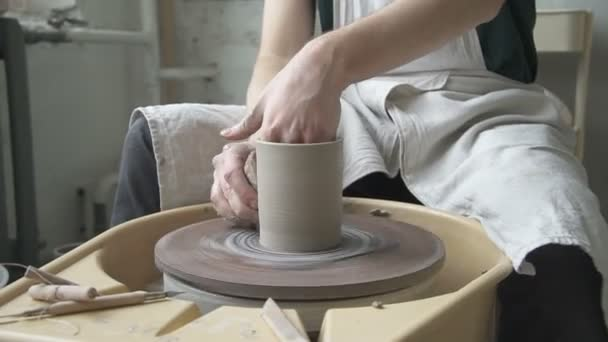 Talented potter is making clay mug in pottery workshop