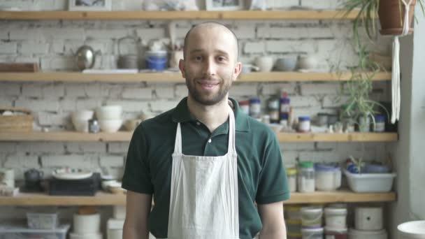 Portrét mužské keramik, který je postavení v jeho ateliéru a dívají se na kameru, pomalý pohyb.