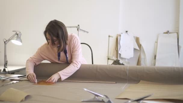 Junge Mode-Designerin arbeitet, macht Markierungen auf Textil mit ...
