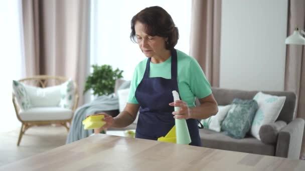 Starší americká hospodyně utírá stůl v domácím pokoji. 4k
