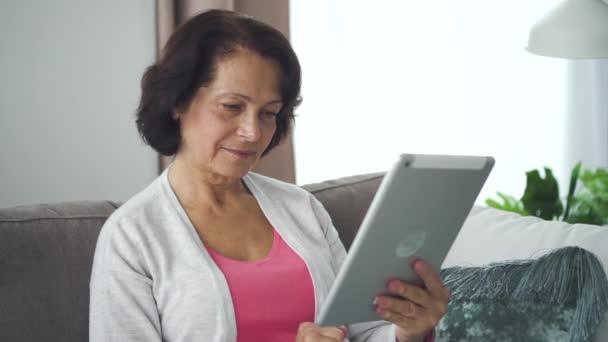 Boldog amerikai üzletasszony használja tabletta ül kanapén a nappaliban.