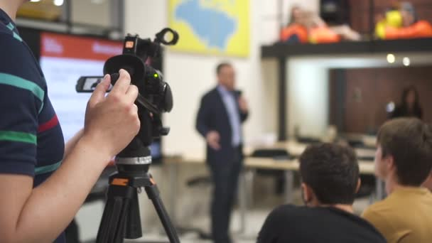 Camera man filming a person giving speech at lecture in audience