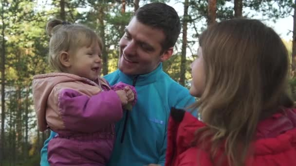 young parents with little daughter in forest or park outdoor portrait