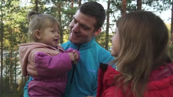giovani genitori con bambina nel bosco o parco ritratto allaperto