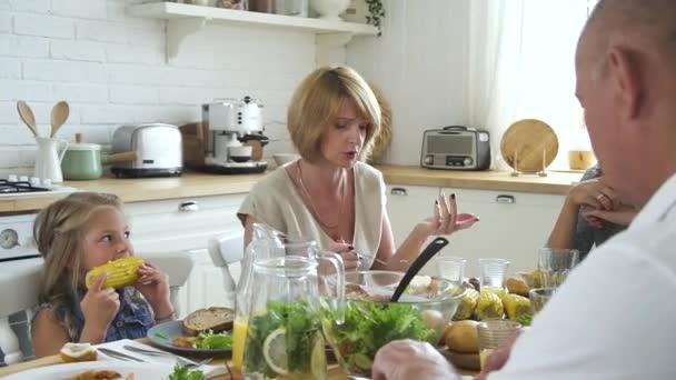 Amerikanische Erwachsene und Kinder treffen sich am festlichen Tisch in der Küche.
