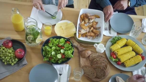 Pohled shora na stůl. čtyři kavkazští přátelé jíst a obědvat