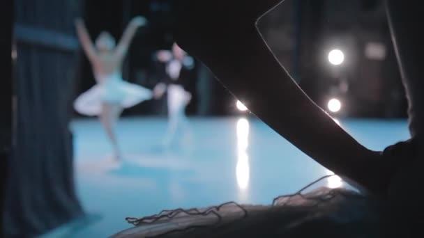 Silhouette einer Ballerina, die hinter der Bühne darauf wartet, auf dem Hintergrund der Ballettaufführung zu erscheinen