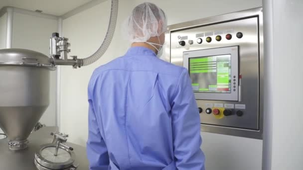 Man employee is working with modern equipment while standing in pharmaceutical company.